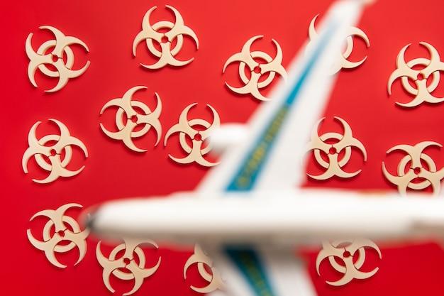 Symbol der biohazard-warnung auf rotem hintergrund mit flugzeug. epidemisches coronavirus-virus. biogefährdung, radioaktiver, giftiger abfall.