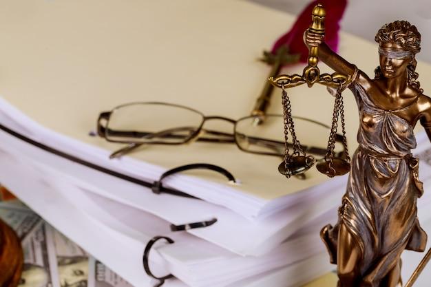 Symbol der gerechtigkeitstatue auf arbeitsdokument der anwaltskanzlei am arbeitsplatz