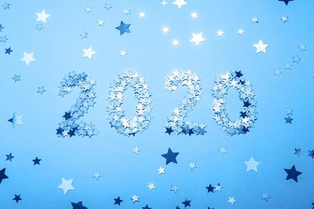 Symbol des neuen jahres 2020 von goldkonfettis auf blauem hintergrund.