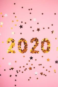 Symbol des neuen jahres 2020 von goldkonfettis auf rosa hintergrund.