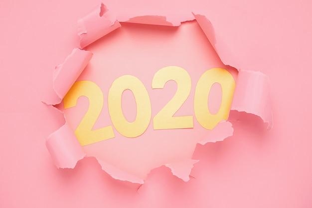 Symbol des neuen jahres der nr. 2020 und des lochs auf rosa papierhintergrund.