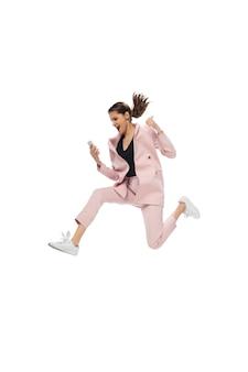 Symbol. glückliche junge frau tanzt in freizeitkleidung oder anzug und macht legendäre bewegungen und tänze von prominenten aus der kulturgeschichte neu. auf weiß isoliert. action, bewegung, ruhm konzept. kreative beschäftigung.
