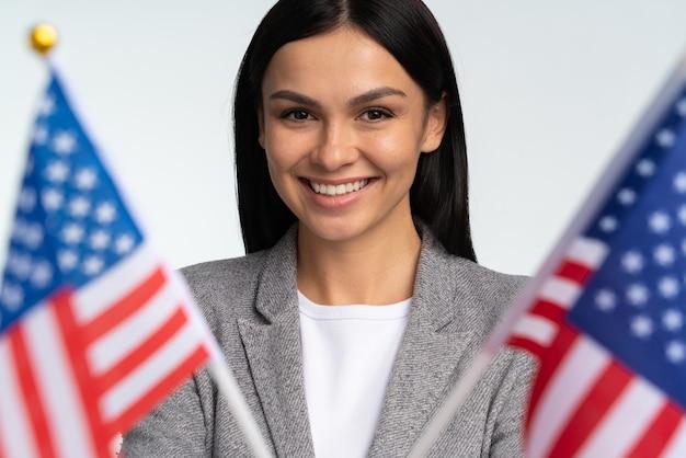 Symbol von amerika, usa-vereinigung. schöne freundliche frau, die breit lächelt und flagge der usa hält. gemeinschaftskonzept