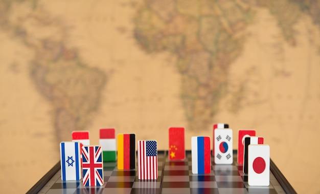 Symbole der länder auf dem schachbrett vor dem hintergrund der politischen weltkarte