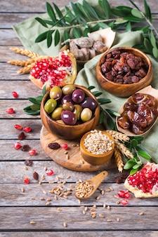 Symbole des jüdischen feiertags tu bishvat, rosh hashana neues jahr der bäume. mischung aus getrockneten früchten, datteln, feigen, trauben, gerste, weizen, oliven, granatapfel auf einem holztisch.