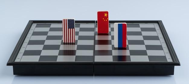 Symbolflagge von russland, den usa und china auf dem schachbrett. das konzept des politischen spiels.