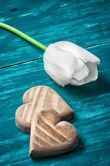 Symbolisches hölzernes herz auf dem hintergrund einer weißen tulpe