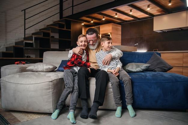 Sympathisch konzentrierter älterer bärtiger großvater mit seinen fröhlichen 10-15-jährigen enkeln, die ihre freizeit damit verbringen, das basketballspiel im fernsehen zu überarbeiten