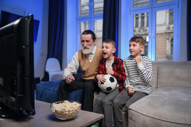 Sympathisch konzentrierter älterer bärtiger großvater mit seinen fröhlichen enkeln, die ihre freizeit damit verbringen, das basketballspiel im fernsehen zu überarbeiten