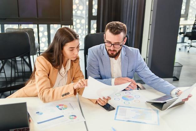 Sympathische, zielgerichtete geschäftspartner studieren finanzdokumente sorgfältig mit diagrammen am besprechungstisch im besprechungsraum.