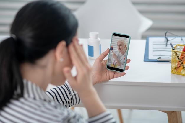 Symptome, ärztliche beratung. dunkelhaarige frau, die ein smartphone betrachtet, das online berät, eine andere hand nahe ihrem kopf.