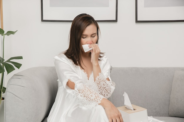 Symptome einer allergischen rhinitis bei frauen kranke frau in weißer nachtwäsche mit einer erkältung, die ihre nase zu hause in ein seidenpapier putzt