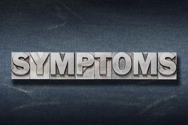 Symptomwort gemacht vom metallischen buchdruck auf dunklem jeanshintergrund