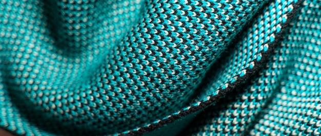 Synthetische strickware mit musterelementen aus blauen, schwarzen und weißen garnen in nahaufnahme.