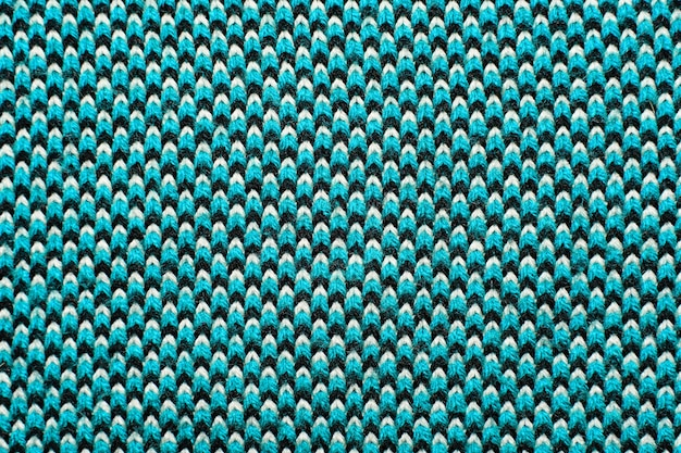 Synthetische strickware mit musterelementen aus blauen, schwarzen und weißen garnen. strickwaren