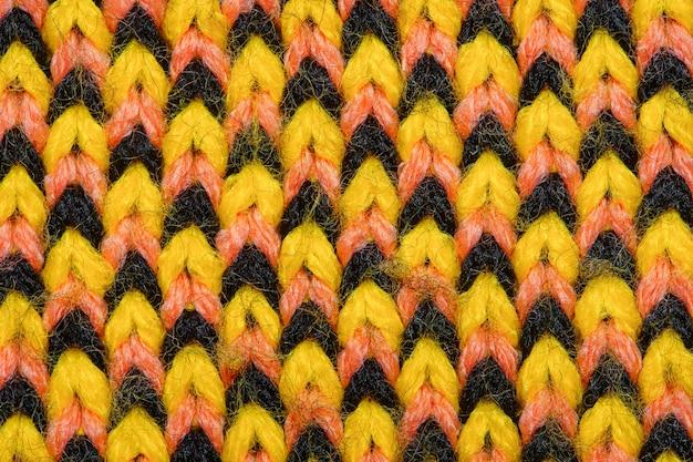 Synthetische strickware mit musterelementen aus gelben, schwarzen und roten garnen in nahaufnahme. hintergrund