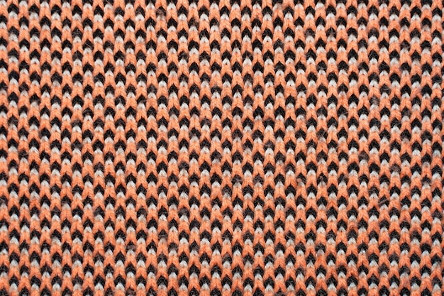 Synthetische strickware mit musterelementen aus roten, schwarzen und weißen garnen in nahaufnahme. strickwaren