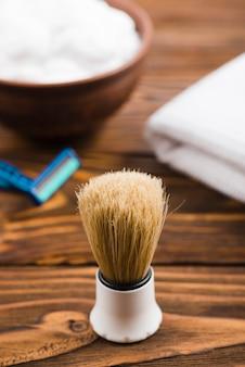 Synthetischer rasierpinsel mit schaum; rasiermesser und gefaltete serviette im hintergrund auf dem tisch
