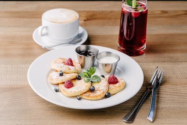 Syrniki mit beeren auf weißem teller lokalisiert auf holztisch in einem café mit saurer sahne und marmelade. hüttenkäsekrapfen. kaffee-beeren-limonade