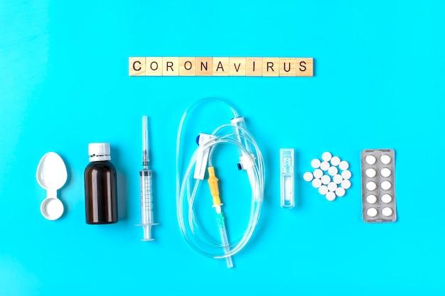 System für tropfer, injektionsspritze, pillen, hustensaft auf blauer oberfläche. coronavirus-wort