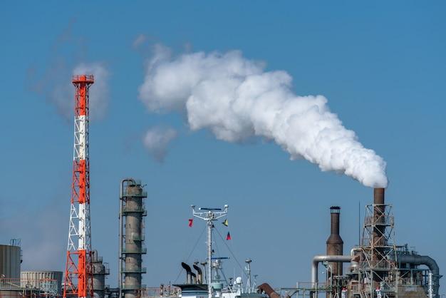 Szene der industriellen zone der erdölraffinerie neben dem fluss auf arbeitsstunde, die dampfrauch haben