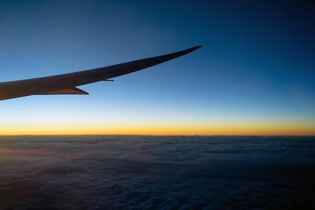 Szene des flugzeugflügels über der wolke und dem fantastischen himmel bei sonnenaufgang