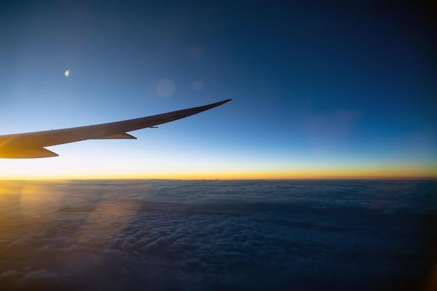 Szene des flugzeugflügels über der wolke und dem fantastischen himmel zur sonnenaufgangzeit, wenn sie über das land fliegen