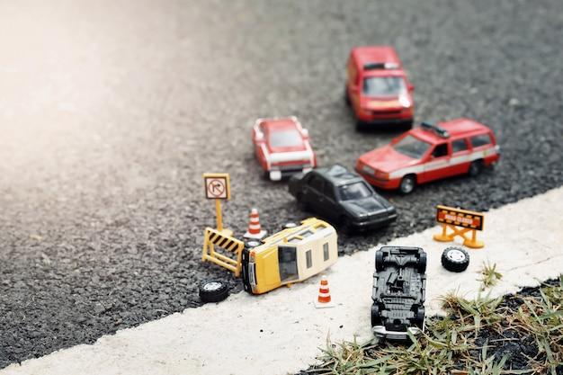 Szene des unfalls der autos (miniatur, spielzeugmodell) auf straße. versicherungskonzept.
