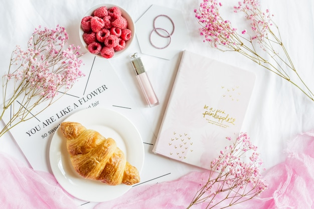 Szene mit hörnchengebäck, frischen himbeeren, notizbuch, lipgloss und rosa blumen.
