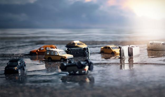 Szene von autos (miniatur, spielzeugmodell) in flut von naturkatastrophen, starkem regen, taifun, hurrikan. transport, autoversicherungskonzept