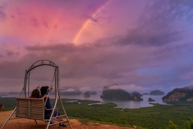 Szene von liebenden, die auf den regenbogen über der fantastischen landschaft von samed sitzen und zeigen