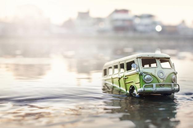Szene von zerschmetterten autos (miniatur, spielzeugmodell) in der flut von naturkatastrophen selektiver fokus.