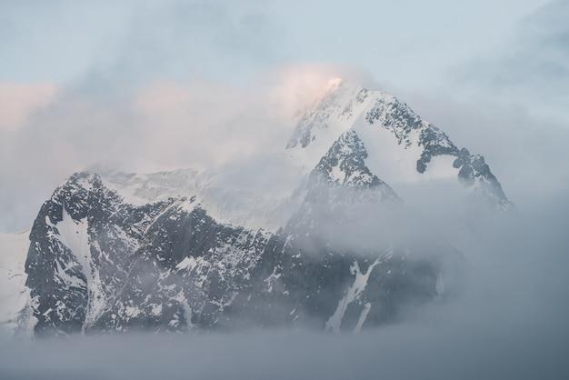Szenische alpine landschaft mit schneebedeckten bergen innerhalb der niedrigen wolken bei sonnenaufgang. schöner gletscher im dichten nebel. weiches morgenlicht durch wolken. geisterhafte landschaft mit rocky mountains in bewölktem himmel in pastelltönen