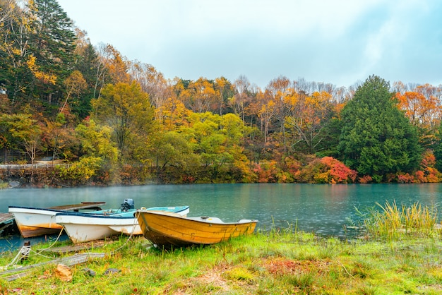 Szenische ansicht des chuzenji-sees im regen mit den booten und dem bunten laub der herbstsaison am ufer bei nikko city in der präfektur tochigi, japan.