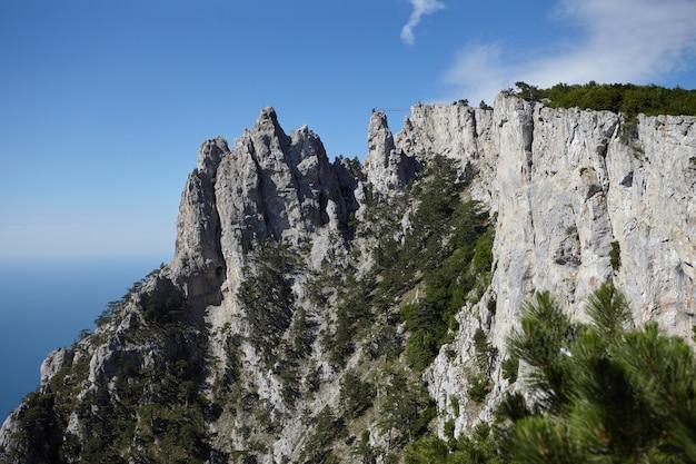 Szenische ansicht des erstaunlichen berges ai-petri gegen blauen himmel und den hintergrund des schwarzen meeres. berge, wandern, abenteuer, reisen, touristenattraktion, landschafts- und höhenkonzept. krim, russland.
