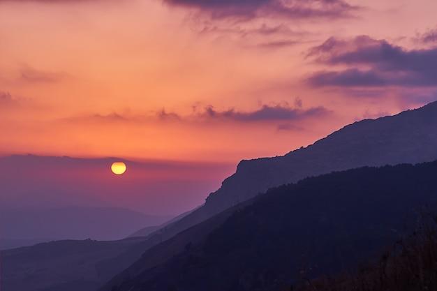 Szenische ansicht des erstaunlichen rosa-gelben sonnenuntergangs in den sizilianischen bergen mit cloudscape