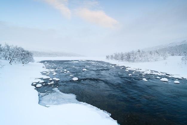 Szenische ansicht des winterflusses grovlan mit schneebedeckten bäumen in der provinz dalarna, schweden