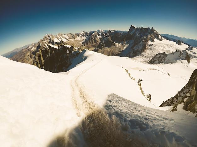Szenische ansicht über schneebedeckte spitzen am sonnigen tag mit blauem reinem himmel