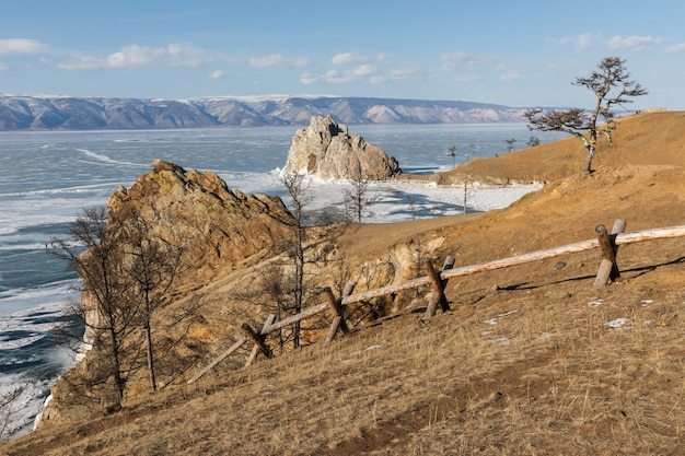 Szenische ansicht von baikalsee von der olkhon insel im winter. blick auf die kleine meerenge, den berühmten shamanka-felsen und den baum der wünsche an einem sonnigen tag.