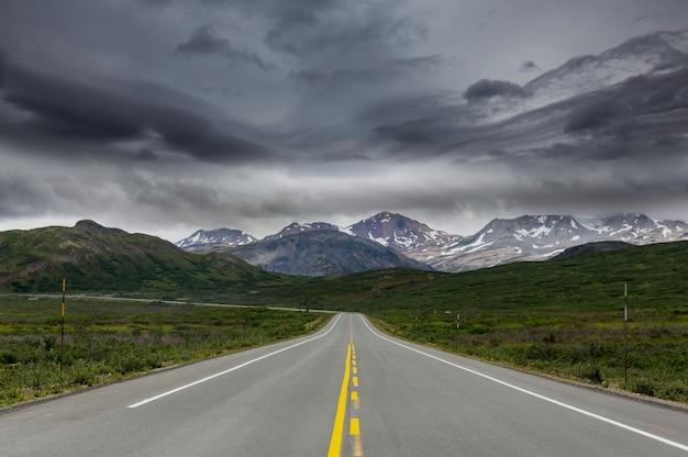 Szenische autobahn in alaska, usa. dramatische ansicht sturmwolken