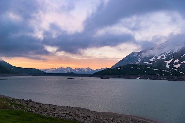 Szenische himmelwolken bei sonnenaufgang, see und schneebedecktem berg, kalter winter, fjord nord gestalten landschaftlich