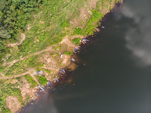 Szenische landschaft der brummenschuss-luftdraufsicht das fischerboot in einem großen fluss mit frischem grünem baum und strand