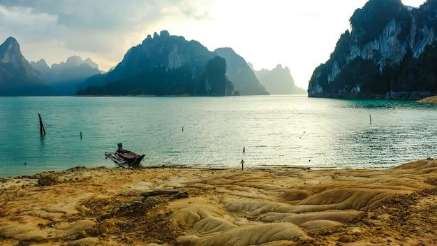 Szenische landschaftsansicht der naturinsel mit sand thailändischem hölzernen longtail-boot und klarem wassergebirgshintergrund des sonnenscheins am cheow lan dam (ratchaprapa-damm) - suratthani thailand.