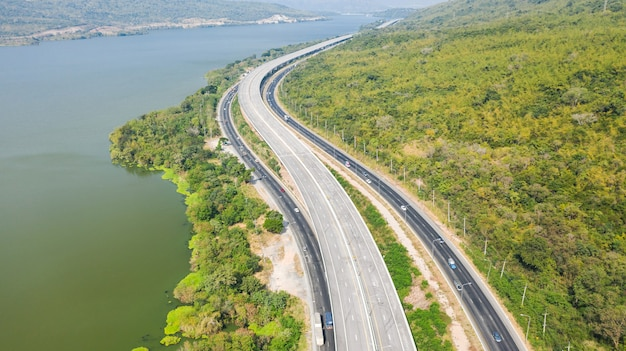 Szenische luftaufnahme der großen autobahn, draufsicht von der drohne der straße und des grünen waldberges in thailand