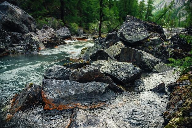 Szenischer naturhintergrund des türkisfarbenen klaren wasserstroms zwischen felsen mit moosen und flechten. stimmungsvolle berglandschaft mit moosigen steinen im transparenten gebirgsbach. schöner gebirgsbach.
