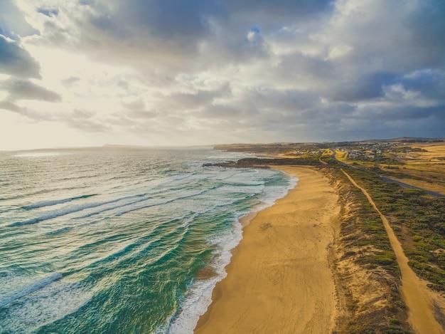 Szenisches panorama der ozeanküste mit gelbem sandstrand und ländlichen gebieten. kilcunda, victoria, australien