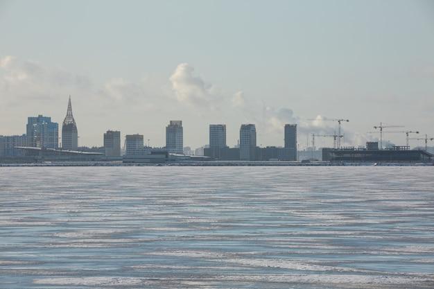Szenisches stadtbild mit wolkenkratzern am ufer des gefrorenen finnischen golfs im winter sankt petersburg, russland.