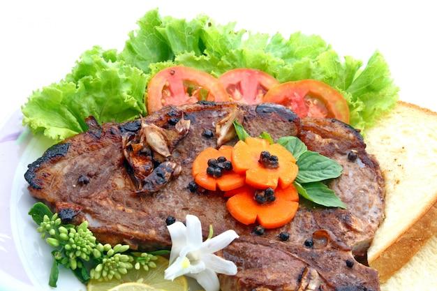 T-knochen-pfeffer-steak mit dem gemüse lokalisiert auf weiß