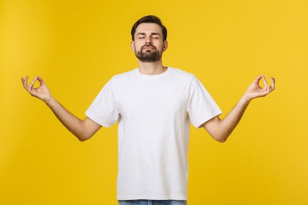 T-shirt des kaukasischen jungen mannes, der isoliert auf grauem studio steht, faltet fingeratemübungsprozess für das reduzieren von stress