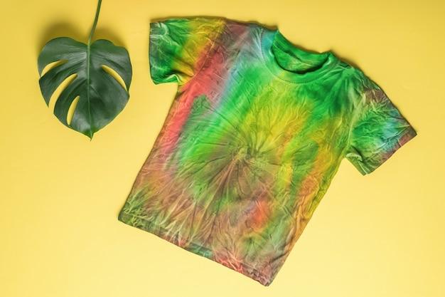 T-shirt im tie-dye-stil auf gelbem grund mit grünem blatt. kleidung zu hause von hand färben. flach liegen.